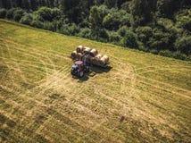 Foto aérea del abejón del granjero Harvesting Hay Rolls en el campo de trigo con un tractor rojo - Sunny Summer Day, apariencia v foto de archivo