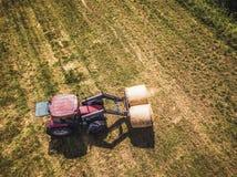 Foto aérea del abejón del granjero Harvesting Hay Rolls en el campo de trigo con un tractor rojo - Sunny Summer Day, apariencia v imagen de archivo