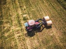 Foto aérea del abejón del granjero Harvesting Hay Rolls en el campo de trigo con un tractor rojo - Sunny Summer Day, apariencia v imagenes de archivo