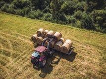 Foto aérea del abejón del granjero Harvesting Hay Rolls en el campo de trigo con un tractor rojo - Sunny Summer Day, apariencia v fotografía de archivo