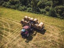 Foto aérea del abejón del granjero Harvesting Hay Rolls en el campo de trigo con un tractor rojo - Sunny Summer Day, apariencia v foto de archivo libre de regalías