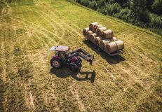 Foto aérea del abejón del granjero Harvesting Hay Rolls en el campo de trigo con un tractor rojo - Sunny Summer Day, apariencia v imagen de archivo libre de regalías