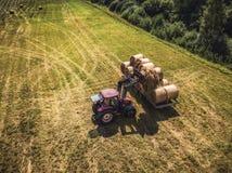 Foto aérea del abejón del granjero Harvesting Hay Rolls en el campo de trigo con un tractor rojo - Sunny Summer Day, apariencia v fotos de archivo libres de regalías