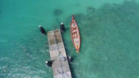 A foto aérea do zangão da vista superior do barco de flutuação na superfície da água e o cais em Rawai encalham em Phuket imagem de stock