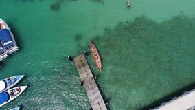 A foto aérea do zangão da vista superior do barco de flutuação na superfície da água e o cais em Rawai encalham em Phuket fotografia de stock