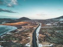 Foto aérea do zangão de uma estrada vazia 1 do lago e da rua com uma montanha vulcânica enorme Snaefellsjokull na distância imagem de stock