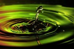 A foto abstrata da água deixa cair no fundo vermelho agradável do verde amarelo Foto agradável da textura e do projeto fotografia de stock