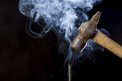 Foto abstrata do martelo oxidado do metal acima do prego com fumo no fundo preto imagens de stock royalty free