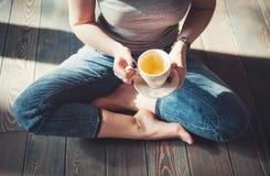 Foto acogedora de la mujer joven con la taza de té que se sienta en el piso Imagen de archivo libre de regalías