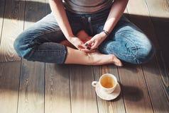 Foto acogedora de la mujer joven con la taza de té que se sienta en el piso Fotografía de archivo libre de regalías