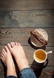 Foto acolhedor dos pés da jovem mulher com chá e bolo no assoalho Imagens de Stock Royalty Free