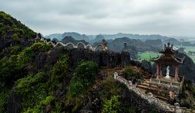 Foto aerea del fuco - donna accanto ad un santuario del drago in cima ad una montagna nel Vietnam del Nord Hang Mua immagini stock