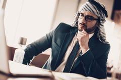 Foto alta vicina del computer portatile considerante arabo fotografie stock