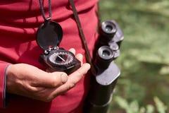 Foto anonima della mano dell'uomo con la bussola, viaggiatore su fondo di legno che porta camicia casuale rossa, posante con il b fotografia stock libera da diritti