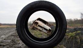 Foto apagado del coche robado que mira a través del neumático Imagen de archivo libre de regalías
