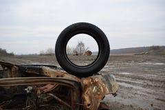 Foto apagados de los coches robados que miran a través del neumático Imagen de archivo libre de regalías