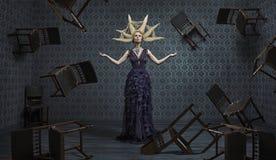 Foto artística de una bruja y de las sillas el elevar y mantener flotando Imagen de archivo