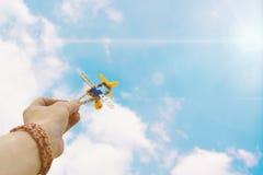 Foto ascendente cercana del aeroplano del juguete de la tenencia de la mano del hombre contra el cielo azul fotografía de archivo