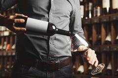 Foto ascendente cercana del vino tinto de colada del sommelier masculino en las copas Camarero con la botella de bebida del alcoh fotografía de archivo