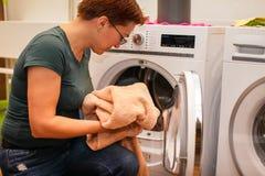 A foto ascendente próxima da mulher caucasiano retira a lavanderia limpa da máquina de lavar imagem de stock