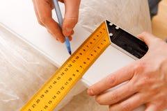 Foto ascendente próxima da régua e do lápis guardando trabalhadores ao fazer marcas na madeira na tabela foto de stock royalty free