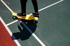 Foto ascendente próxima do homem moderno no desgaste à moda que mantém os pés no skate amarelo fotografia de stock
