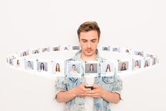 Foto ascendente próxima interessada ele seu smartphone da posse do indivíduo dedicado em linha senta o Internet para escolher par fotografia de stock