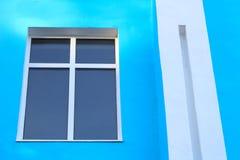foto astratta di una finestra scurita con un incrocio della divisione su una parete blu e su una colonna rettangolare bianca fotografie stock