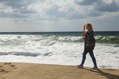 Foto atmosférica da mulher só que anda no mar tormentoso imagem de stock
