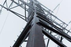 Foto atmosferica del primo piano della prospettiva della torre ad alta tensione della trasmissione coperta di brina che sta sopra Fotografia Stock