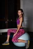 Foto auf Lager: Junge hübsche Eignungsfrau auf einem Sitzball Stockbild