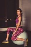 Foto auf Lager: Junge hübsche Eignungsfrau auf einem Sitzball Stockfotos