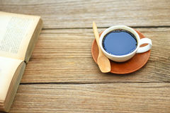 Foto auf Lager - offenes Buch mit Tasse Kaffee auf rustikaler hölzerner Rückseite Stockfotografie