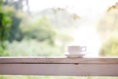 Foto auf Lager - weiße Kaffeetasse auf Schiene mit grünem Natur backgro stockfotos