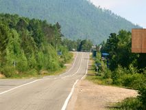 Foto av att gå tillbaka in i avståndet av vägrutten på bakgrunden av bergmaxima med gräsplan skogarna Arkivfoton