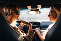 Foto av baksida av två blonda kvinnor med den långa hår och telefonen i handen som sitter i bil fotografering för bildbyråer