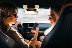 Foto av baksida av två talande kvinnor med långt hår med telefonen i händer som sitter i bil arkivbilder