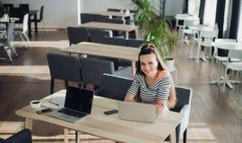 Foto av barn som ler kvinnligt sammanträde i ett kafé som coworking, medan genom att använda bärbar datordatoren som pratar vid t Arkivbild