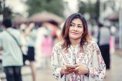 Foto av den asiatiska kvinnan som ser telefonen Royaltyfri Fotografi