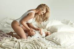 Foto av den blonda modern för förtjusande youn som spelar med hennes nyfödda lodisar Royaltyfria Bilder