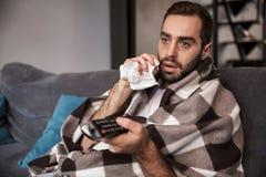 Foto av den europeiska man30-tal som slås in i filten som ser sjuk, medan sitta på soffan i lägenhet royaltyfria bilder