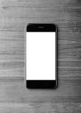 Foto av den generiska designsmartphonen på grå wood bakgrund vertikalt Royaltyfria Bilder