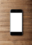 Foto av den generiska designsmartphonen på wood bakgrund vertikalt Arkivbild