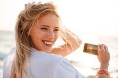 Foto av den glade blonda kvinna20-tal som ler och tar fotoet av su fotografering för bildbyråer