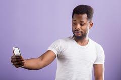 Foto av den h?pna f?rbryllade svarta mannen som rymmer den moderna mobiltelefonen royaltyfri foto
