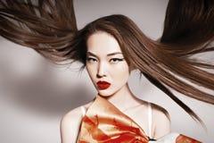 Foto av den härliga asiatiska kvinnan med storartat hår. arkivfoto
