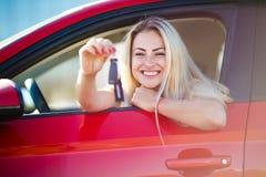 Foto av den härliga blonda kvinnan med tangenter som sitter i röd bil med det öppna fönstret royaltyfria foton
