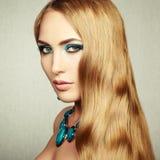 Foto av den härliga kvinnan med storartat hår. Perfekt makeup fotografering för bildbyråer