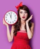Foto av den härliga unga kvinnan med klockan på den underbara purplen Royaltyfria Bilder