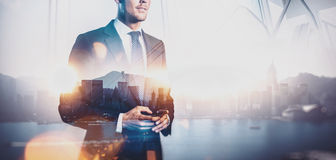 Foto av den hållande smartphonen för affärsman Dubbel exponering, stad på bakgrunden wide royaltyfri bild
